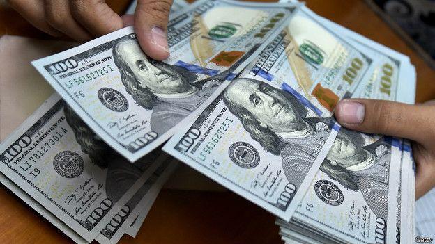 Un cajero cuenta billetes de 100 dólares