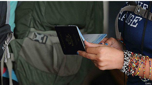 Una mujer sostiene un pasaporte en sus manos.