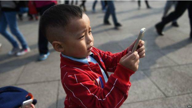 AFP Image caption Ada kekhawatiran bahwa anak-anak kini rentan mengalami kecanduan ponsel.