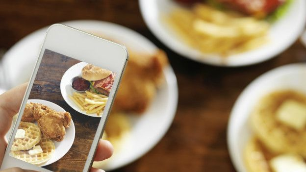Una persona fotografiando unos platos de comida