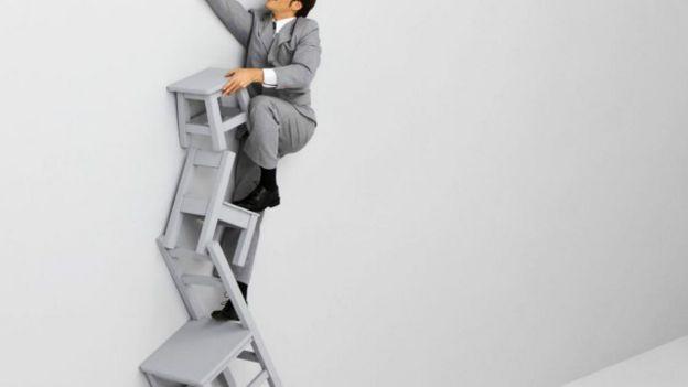 Persona escalando a través de varias sillas.