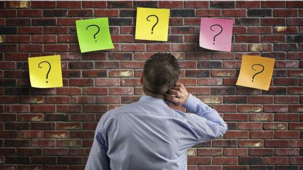Una persona frente a varios signos de interrogación