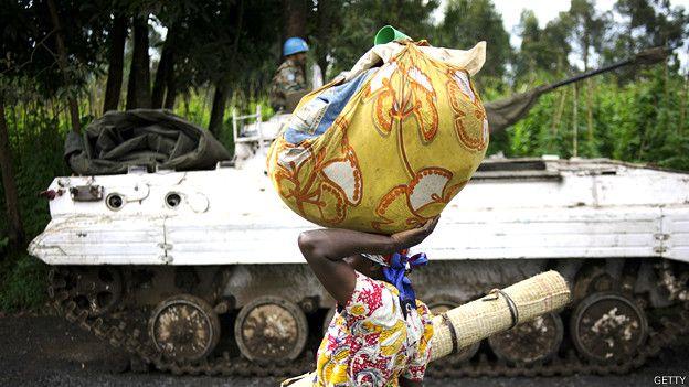 Una mujer en África camina con un bulto de ropas en su cabeza frente a un tanque conducido por soldados de la ONU