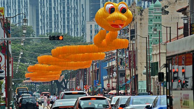 Уличный фонарь в форме извивающегося змея над сингапурской улицей