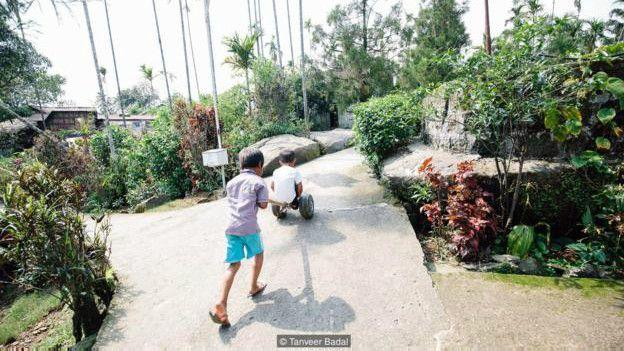 Image caption Anak-anak bermain di jalanan desa Mawlynnong (Credit: Tanveer Badal)