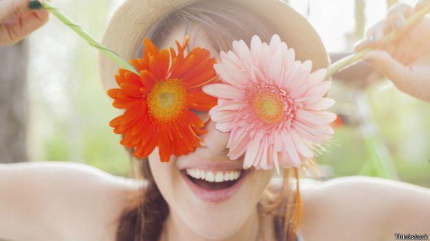 Mujer sonriendo y cubriendo los ojos con flores
