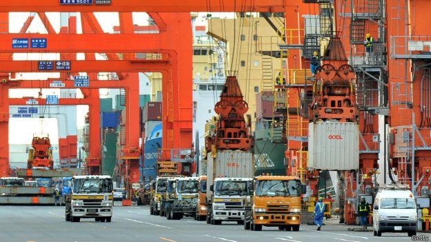 Grúas cargan contenedores a un barco en un puerto chino
