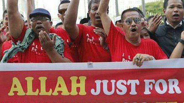 Малайские мусульмане с плакатом