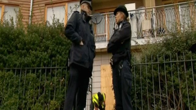 شرطيان يقفان أمام المنزل الذي احتجزت فيه النساء
