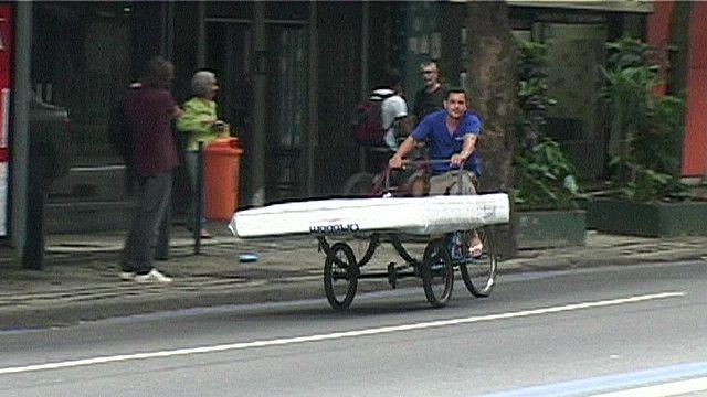 Un hombre lleva un colchón en su bicicleta