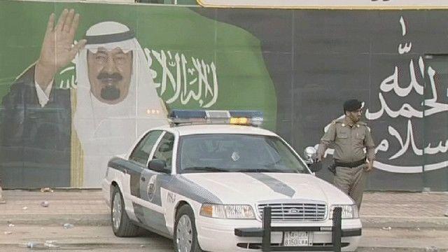 سيارة شرطة أمام صورة للملك السعودي