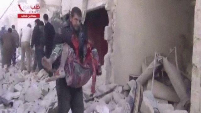 رجل يحمل طفلا ضحية القصف على حلب