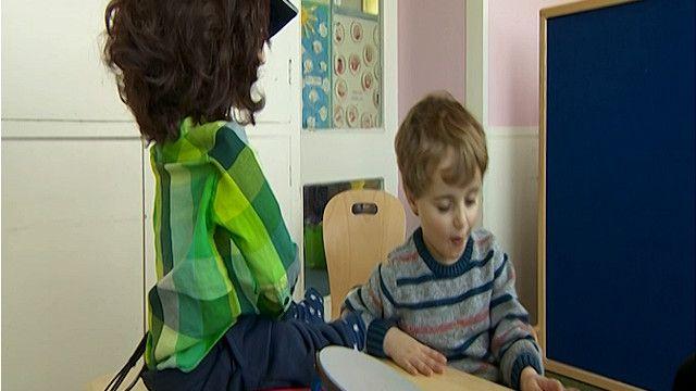 طفل يجلس امام رجل آلي