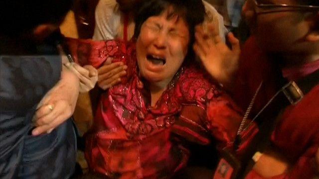 Familiar de passageiro do voo MH 370 é retirada por autoridades de local em que entrevista coletiva estava sendo realizada (BBC)