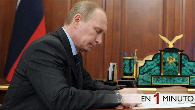 Vladimir Putin firmando documentos en el Kremlin