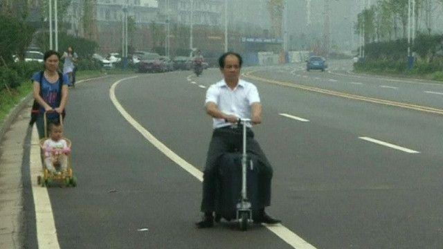 صيني يقود حقيبة سفر
