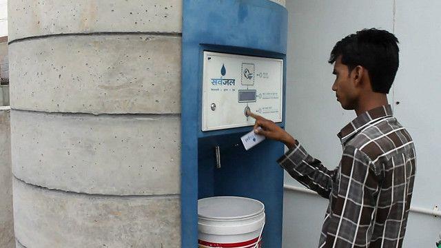 Мужчина пользуется автоматом с питьевой водой