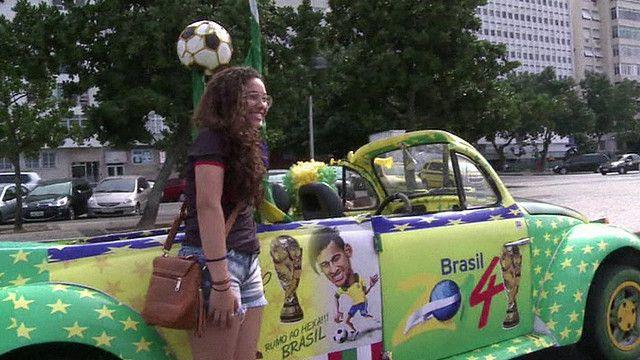 مشجعة برازيلية تتصور بجانب سيارة مزينة برموز الفريق