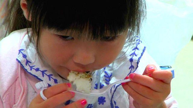 Девочка ест рис из Фукусимы