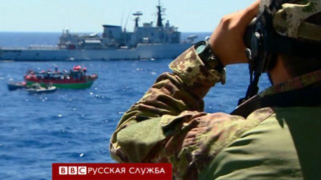 Итальянский военный корабль возле лодки с мигрантами