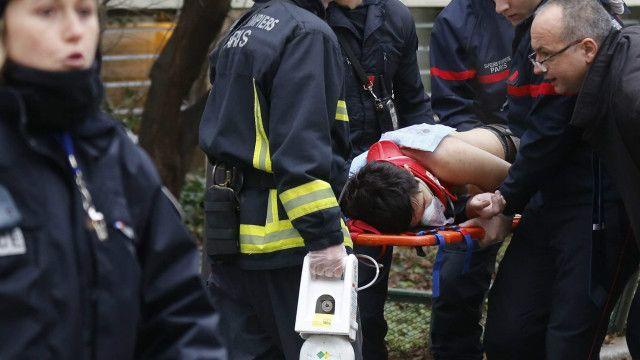 Policías transportan herido por ataque a revista Charlie Hebdo