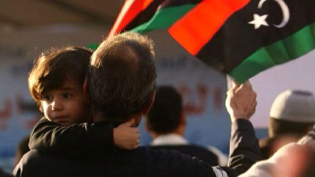 Мужчина держит ребенка на демонстрации в Триполи