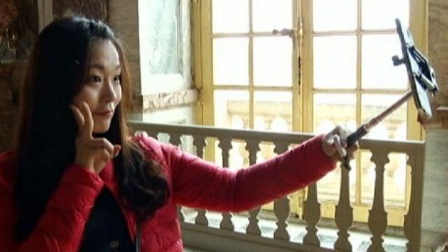 Девушка фотографирует себя с помощью палки для селфи в Версале