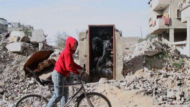 Палестинский подросток на велосипеде на фоне граффити Бэнкси