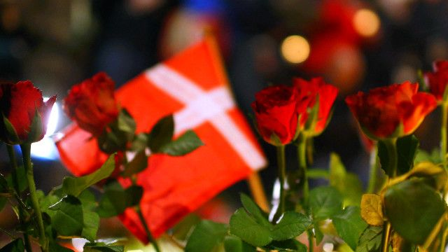 Флаг и цветы на месте нападения в Копенгагене