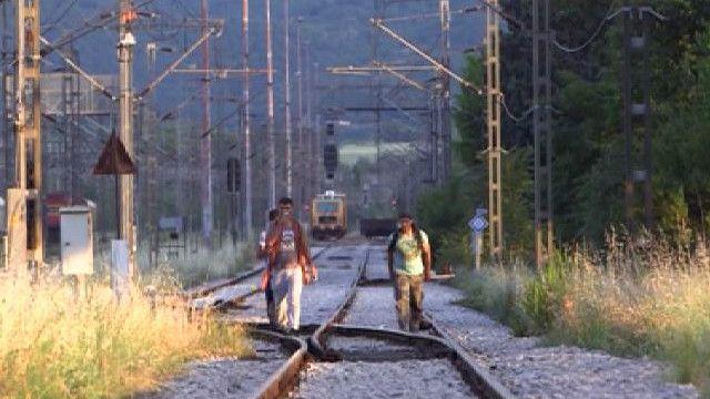 Мужчины идут по железнодорожным путям