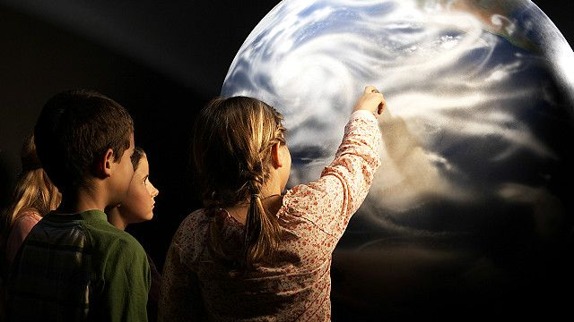 Schoolchildren looking at a globe