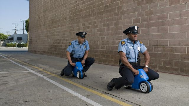 two men sitting on toy cars