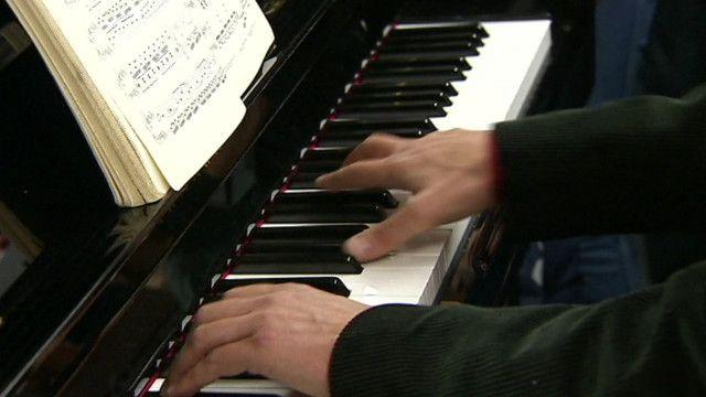 برسلز میں ایک زیر زین ٹرین میں پیانو ساز پیانو بجا رہا ہے