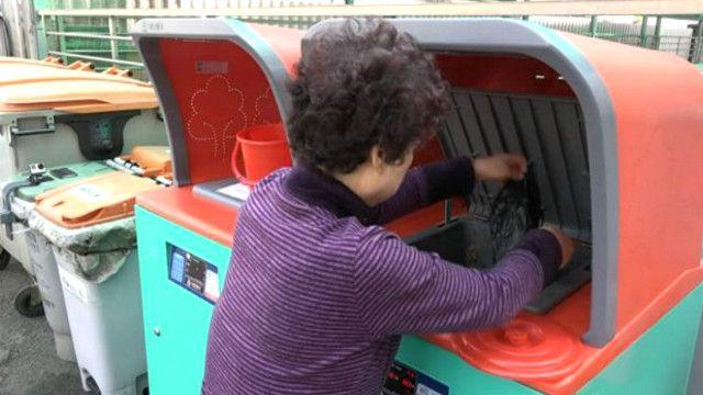 Жительница Сеула выбрасывает мусор в мусороприемник