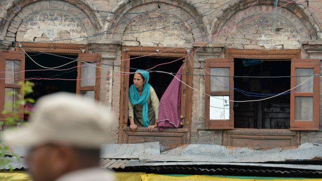 سرینگر میں کرفیو کے دوران ایک خاتون کھڑکی سے باہر دیکھ رہی ہیں