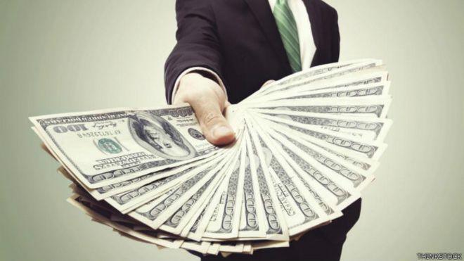 Una persona con un fajo de billetes en la mano