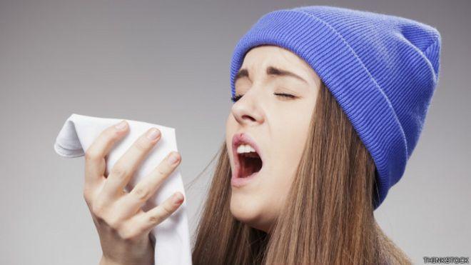 Una joven estornudando
