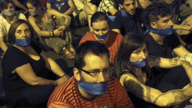 """Manifestación en Madrid frente al Congreso la víspera de la entrada en vigor de la nueva Ley de Seguridad Ciudadana, conocida popularmente como """"Ley Mordaza""""."""