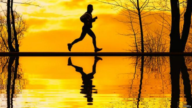 Una persona corriendo con el atardecer de fondo