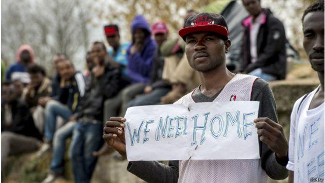 """un inmigrante del campamento de refugiados en Calais sostiene una pancarta: """"We Need Home"""" (necesitamos un hogar)"""