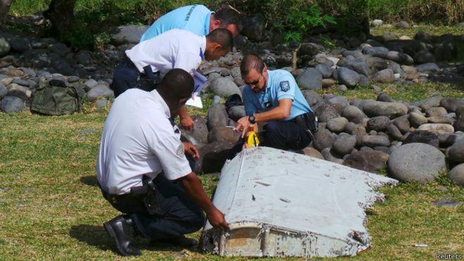 equipo de policías recoge alerón en playa de isla la Reunión