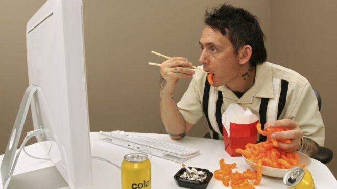 Hombre comiendo frente a computador