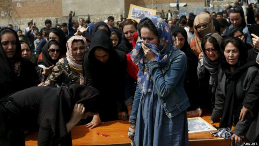 Mujeres lloran junto al féretro