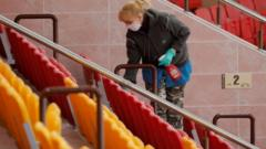 A woman wearing a protective mask and gloves cleans the seating area