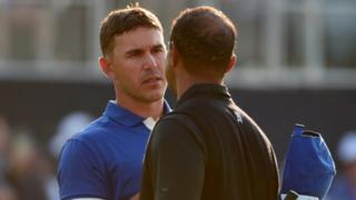 Brooks Koepka greets Tiger Woods after their contrasting rounds