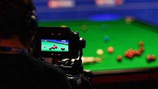 Cameraman filming snooker match