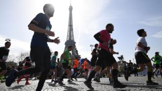 Paris Marathon runners pass the Eiffel Tower