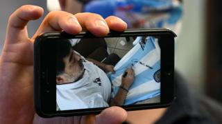 Maradona appears on a person's phone screen