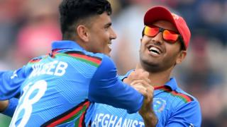 Afghanistan's Mujeeb celebrates taking a wicket