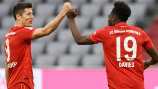Robert Lewandowski (left) celebrates a Bayern Munich goal with team-mate Alphonso Davies